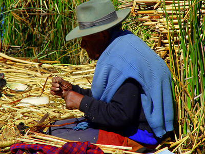 The men make model reed boats to sell to the tourists.