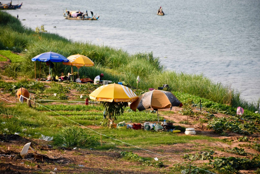 There were many barely floating boats along the riverbank that housed many small communities. They used the shoreline to plant small gardens.